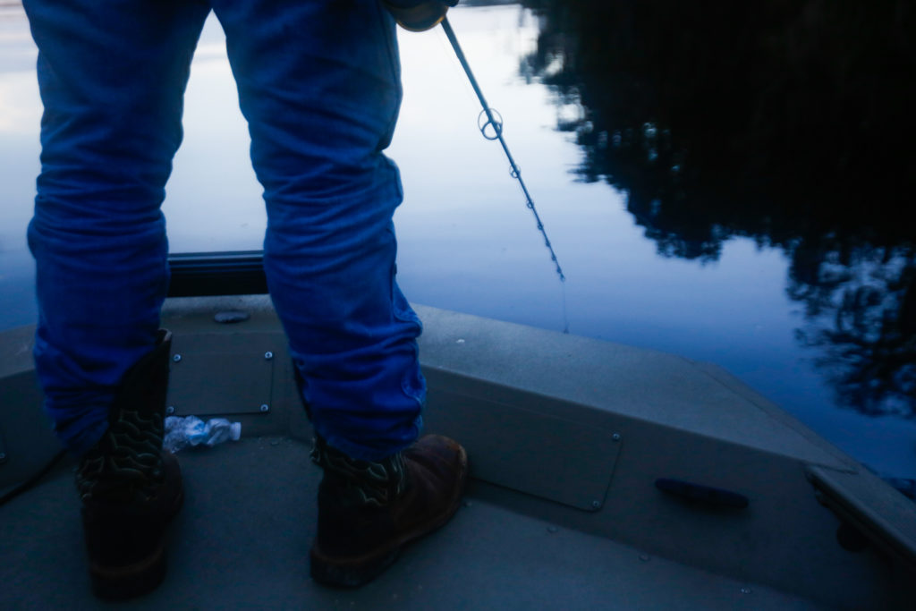 Richie Smith stands at the front of the boat looking closely at the water for signs of an alligator after previously spotting one nearby on October 26, 2019. [CHRIS DAY/Fresh Take Florida]