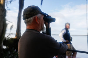 Richie Smith looks through binoculars after Alex Horton moved the boat near the shoreline in search of alligators on October 26, 2019. [CHRIS DAY/Fresh Take Florida]