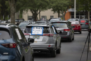 """Cars loop around a plaza as part of a teacher protest. One sign says """"We need a better plan."""""""